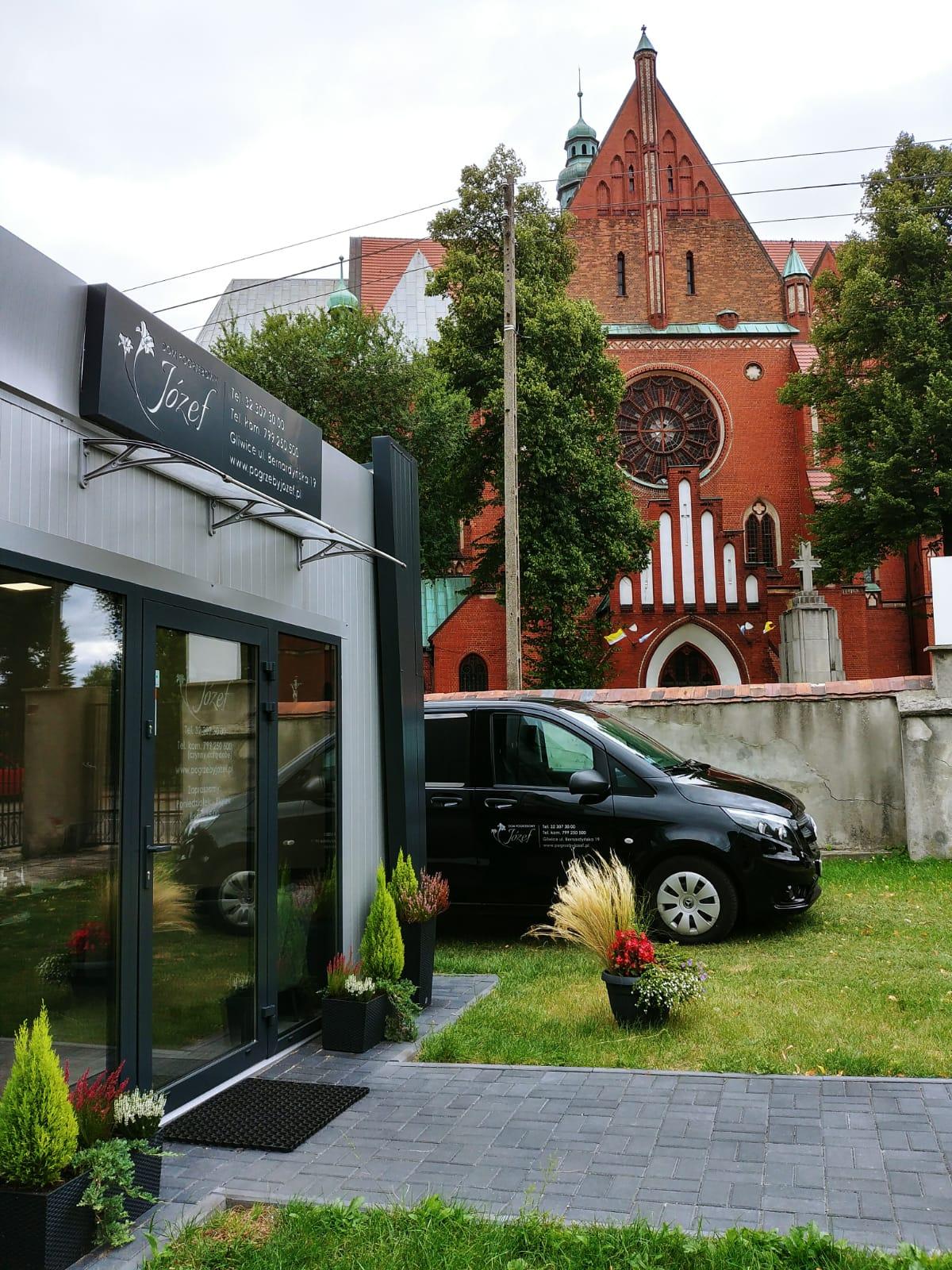 Dom pogrzebowy Józef z zewnątrz z samochodem - w tle kościół Św Bartłomieja
