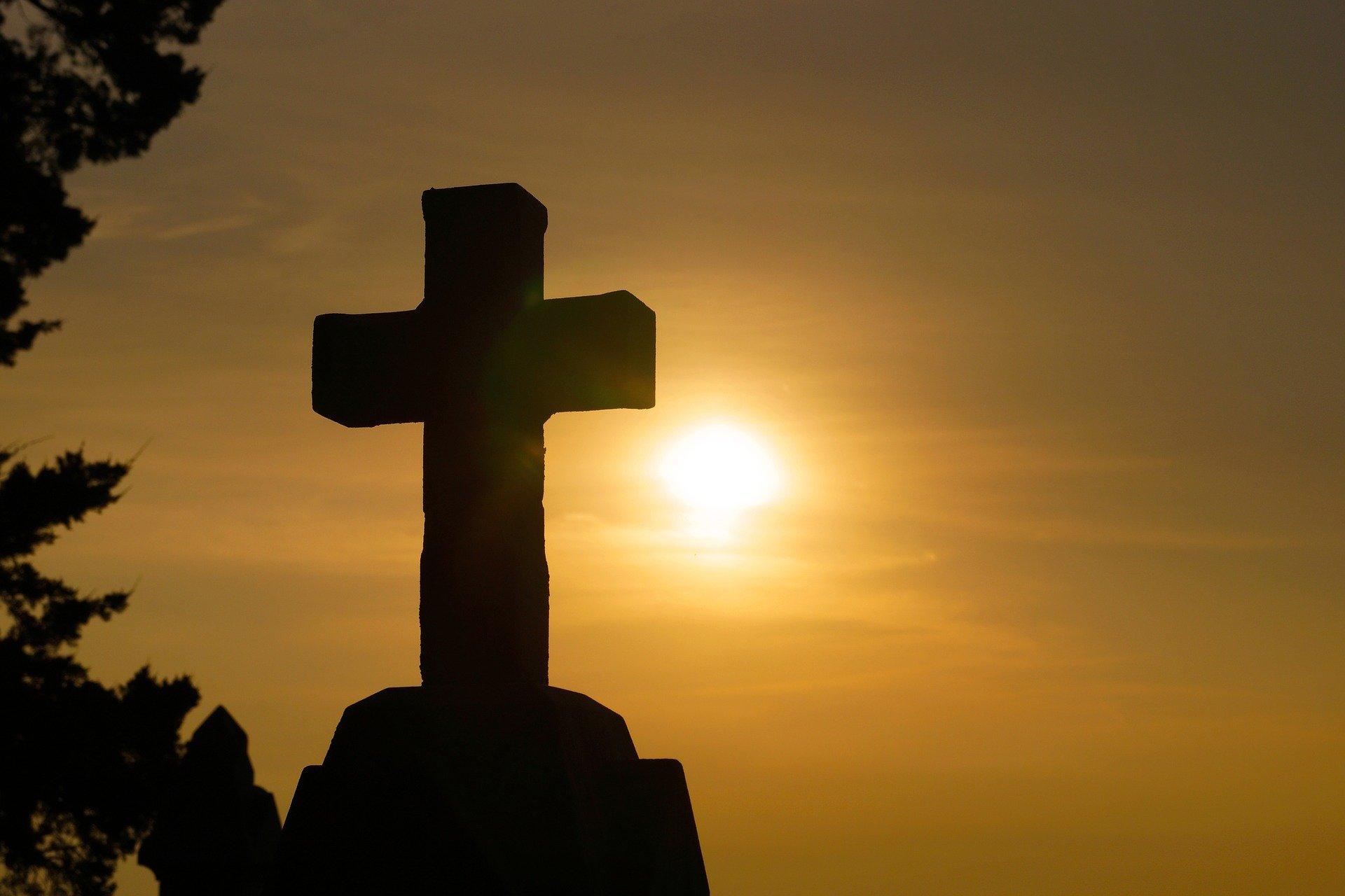 kamienny krzyż na tle słońca
