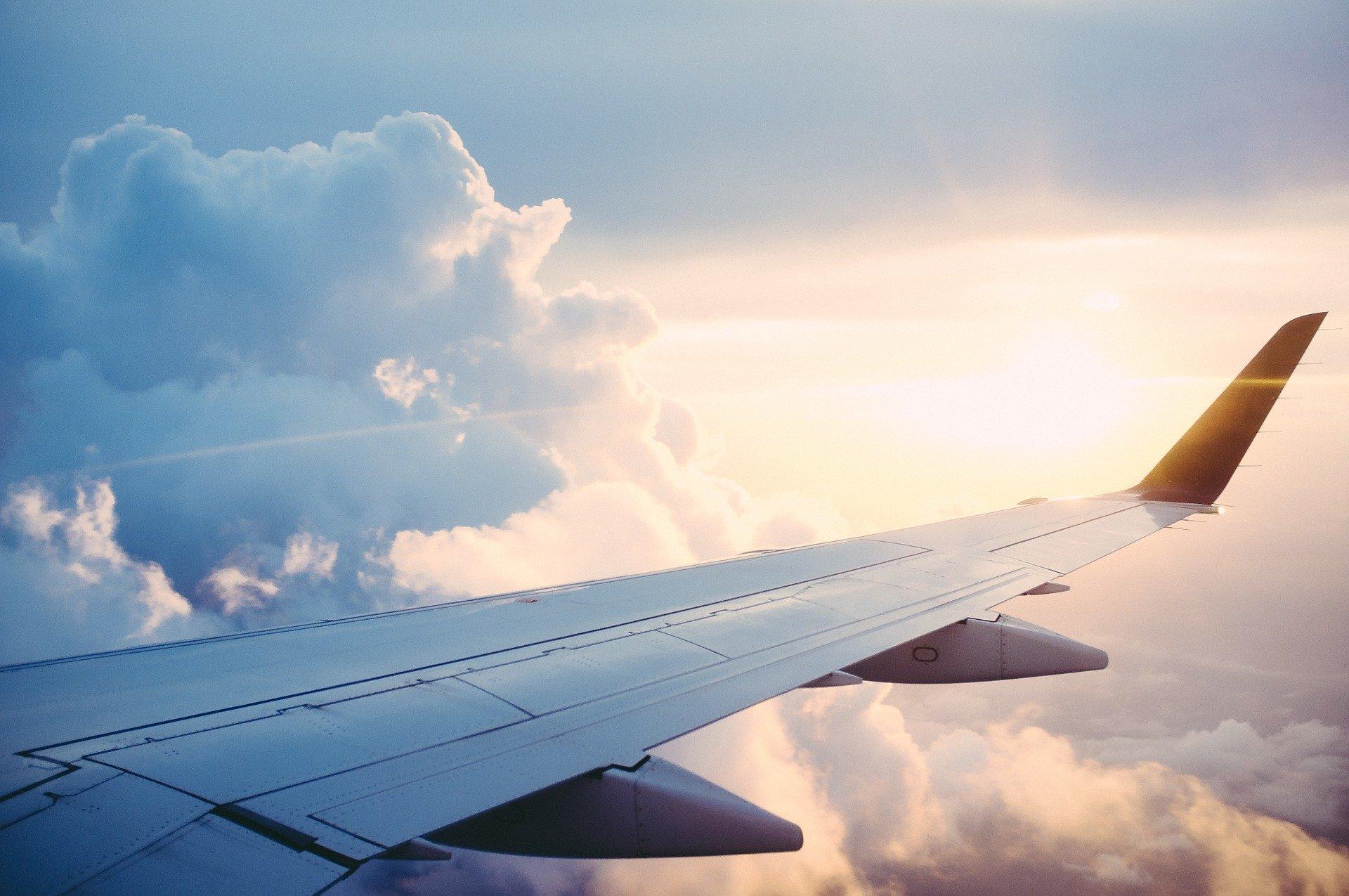 skrzydło samolotu na tle zachodzącego słońca
